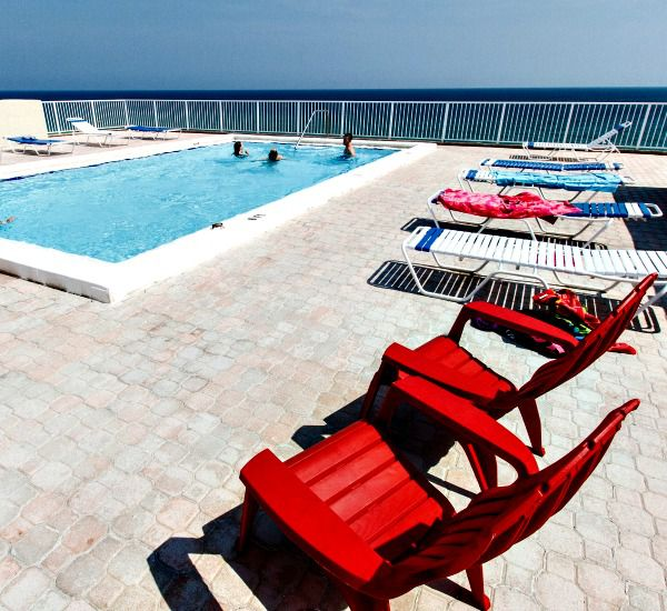 Coloful beach chairs and loungers line the poolside sundeck at Gulfside Condo Fort Walton Beach.