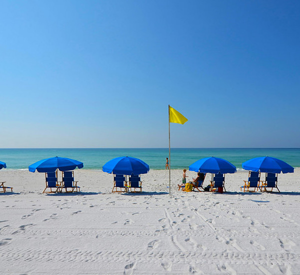 Blue umbrellas shade pairs of beach chairs on the sands at Island Princess Fort Walton.