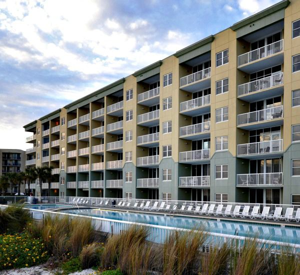 Beach-side exterior view of the property and pool at Waters Edge Condos