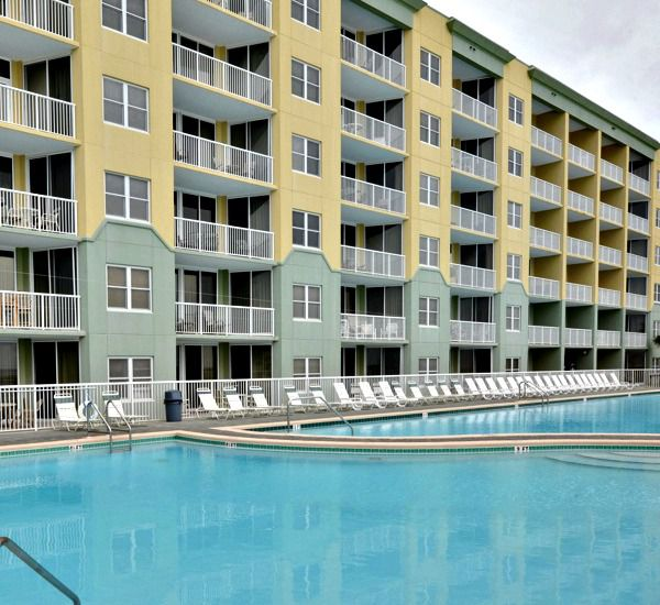 Beach-side exterior view and Gulf-front swimming pool at Waters Edge Condos