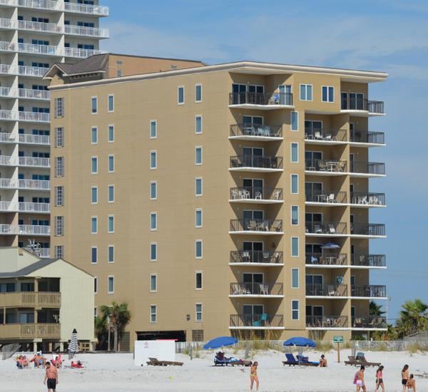 Beachgoers enjoying the sun and sand outside Legacy Gulf Shores