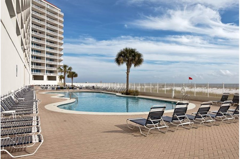 Comfortable lounge chairs flank the beachfront pool at the Lighthouse Gulf Shores.