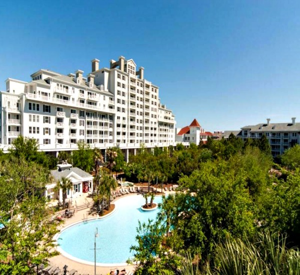 Exterior view with wooded grounds and swimming pool at Bahia in Sandestin Florida.