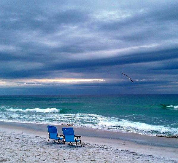 Pair of blue lounge chairs on the beach at Gulf Winds East Destin FL