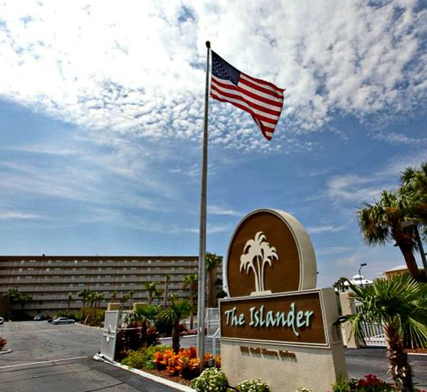 Street-side marquee with landscaping and American flag at The Islander Destin