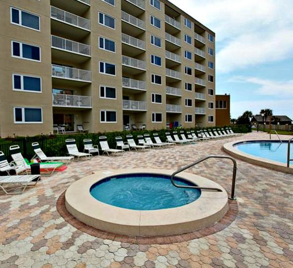 Pool deck with hot tub and lounge chairs at The Islander Destin