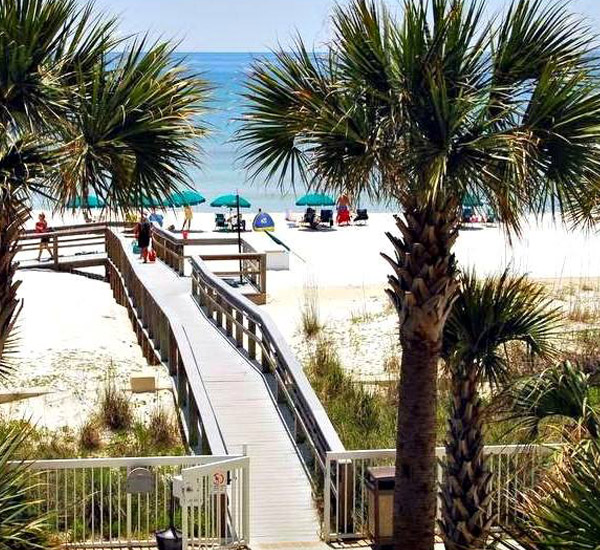 Palm trees flank the beach boardwalk entrance at Azure Fort Walton Beach