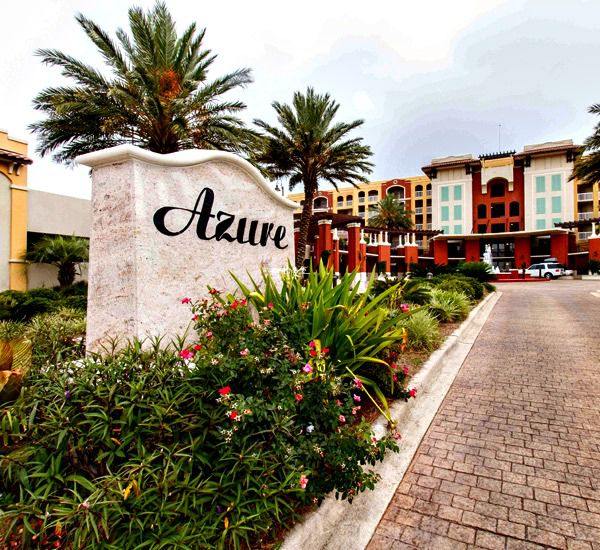 Tropical landscaping surrounds the street-side sign at Azure Fort Walton Beach.