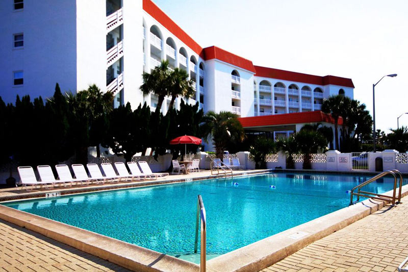 Swimming pool and sundeck with lounge chairs at El Matador Fort Walton Beach