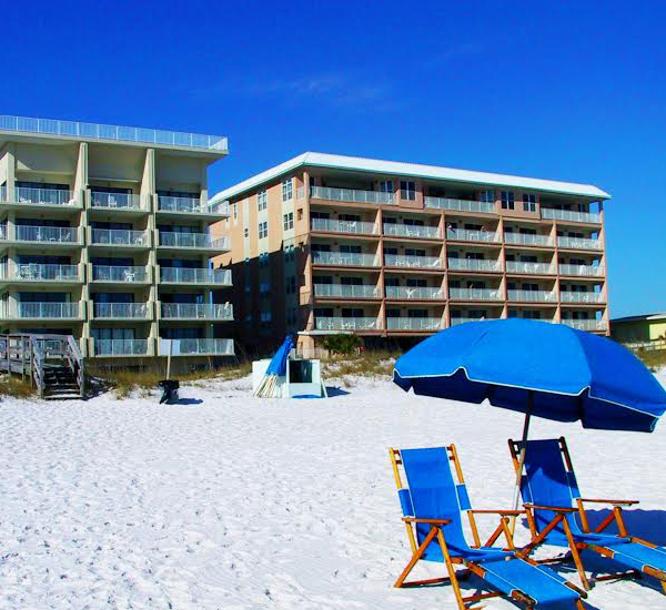 Pair of blue lounge chairs and matching umbrella on the beach at Gulfside Condo Fort Walton Beach