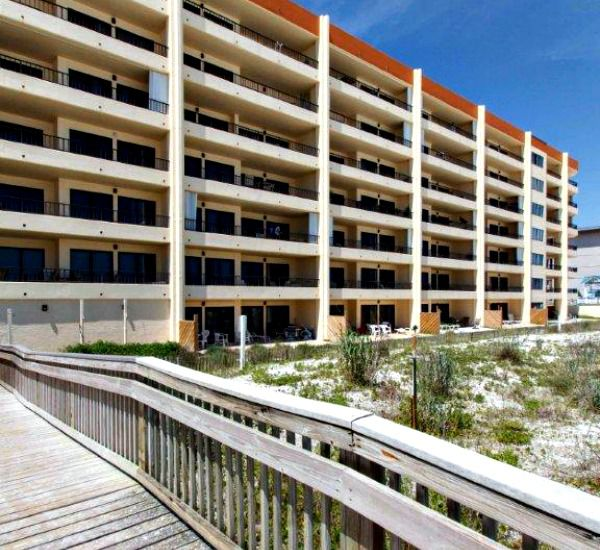 Gulf-side exterior view and beach boardwalk at Surf Dweller Fort Walton Beach