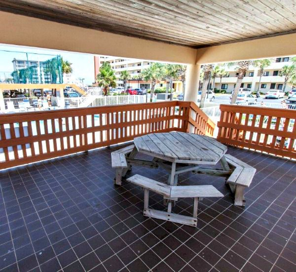 Interior of covered picnic area with table and benches at Surf Dweller Fort Walton Beach