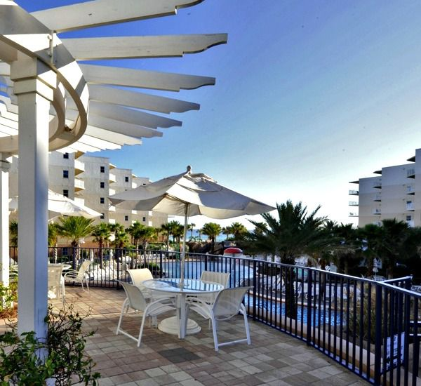 Patio with covered seating overlooking the pool area at Waterscape Resort in Fort Walton Beach
