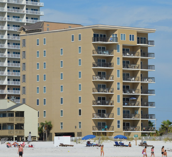 Beachgoers enjoying the sun and sand outside Legacy Gulf Shores