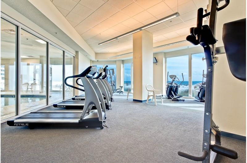 Walls of windows offer views of the beach and Gulf in the workout room at the Lighthouse Gulf Shores.