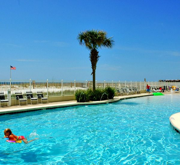 A single swimmer enjoys the beachfront pool at the Lighthouse Gulf Shores.