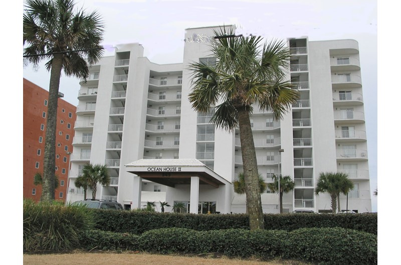 Palm-shaded exterior view from the street at Ocean House Gulf Shores