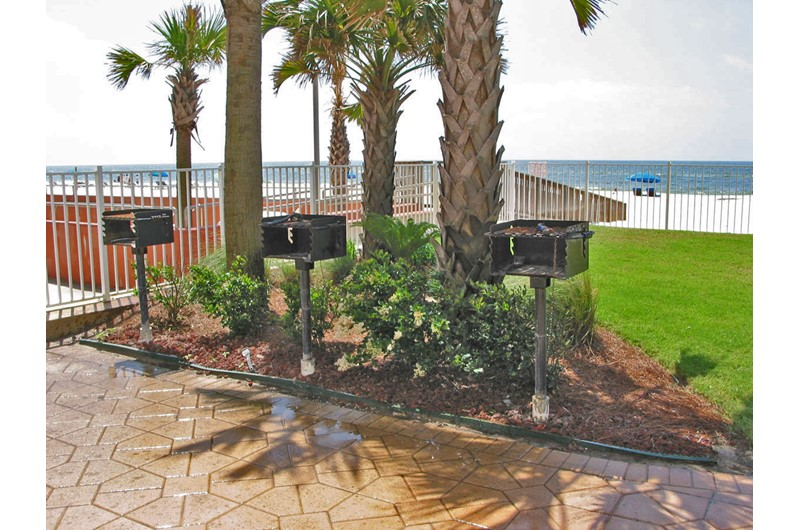 Grilling area with three grills and a view of the beach at Ocean House Gulf Shores
