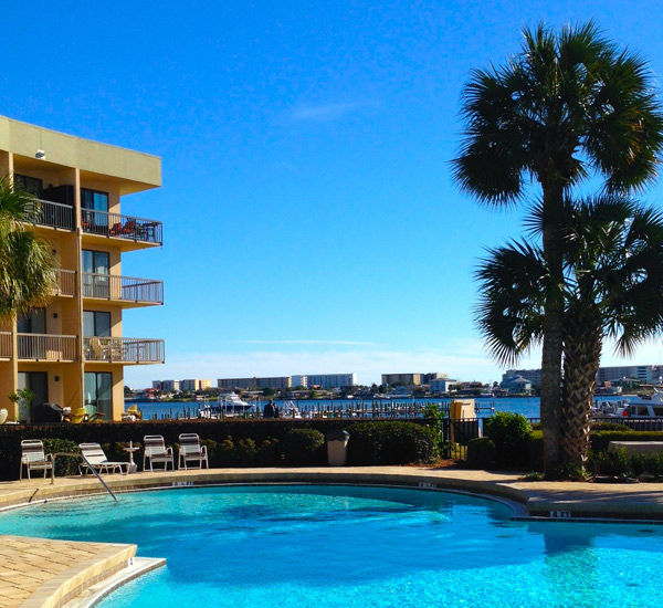 Exterior of property and close up of palm shaded pool at Pirates' Bay Guest Chambers & Marina in Fort Walton Florida